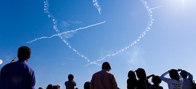 代替医療|青空にハートのマークの飛行機雲、それを見上げる人々