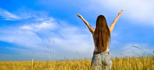 骨の形成|女の人が大草原で青空に向かって大きな手を広げている姿