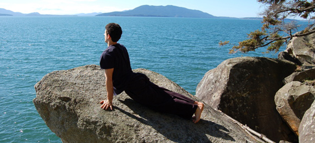 椎間板ヘルニア|岩の上でうつ伏せから上体を反らすポーズをとっている男性